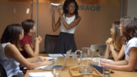 Black female boss stands addressing team at business meeting video