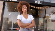 Black female owner walks into focal plane outside coffee shop video