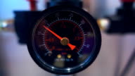 Black gauge with red arrow indicate surges of pressure in the equipment video