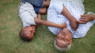 Black grandad and grandson play lying on grass, aerial view video