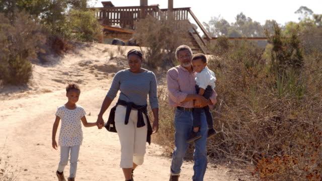 Black grandparents walking with grandchildren, front view video