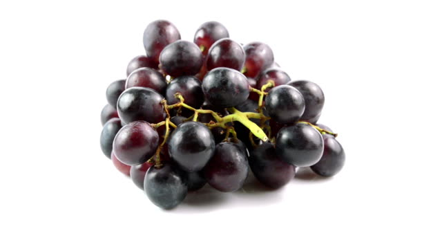 Black grapes on white background video