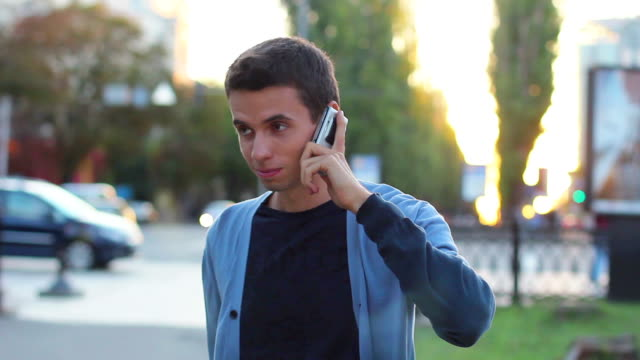 Black haired male calling phone talking in park hangs up video