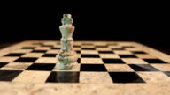 A black king hits a white king on an empty chess board, isolated on black background video