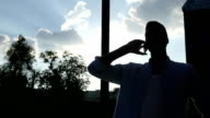 Black Man  Talking on Phone, in front of Sun during Sunset, Silhouette video