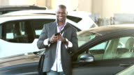 Black man walking thru parking lot looking at phone video