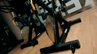 Black modern stationary bikes in a trendy fitness club video