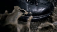 Black new and glossy boots step on a puddle. Slow mo, slo mo video