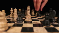 A black queen hits the white king and throws him down on a chess board video