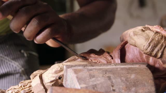 Black sculptor, artist, art, wooden statue, hands, tool video