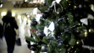 Black shiny and matte balls and white bow. New Year's and abstract blurred shopping mall background with Christmas tree decorations video