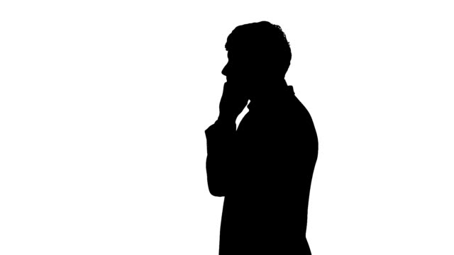 Black silhouette of man typing on mobile telephone video