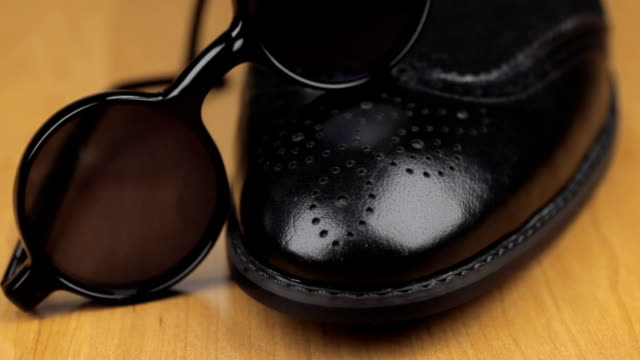Black sunglasses are on black men's shoes. Dolly shot. video