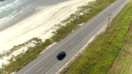 AERIAL: Black SUV car driving on countryside road along the Bay of Mexico video