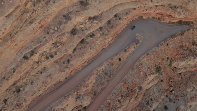 AERIAL TOP DOWN: Black SUV car driving on gravel hairpin road in red mesa cliff video