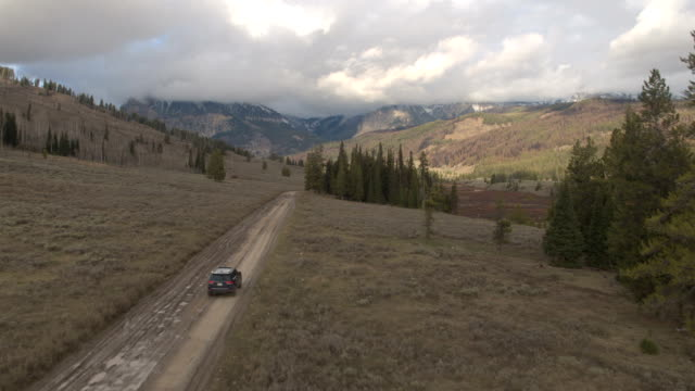 AERIAL Black SUV car driving on road trough river valley towards Rocky Mountains video