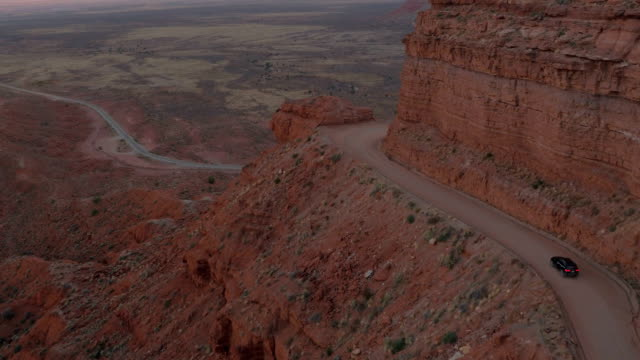 AERIAL Black SUV car driving on winding hairpin road in red mesa mountain cliff video