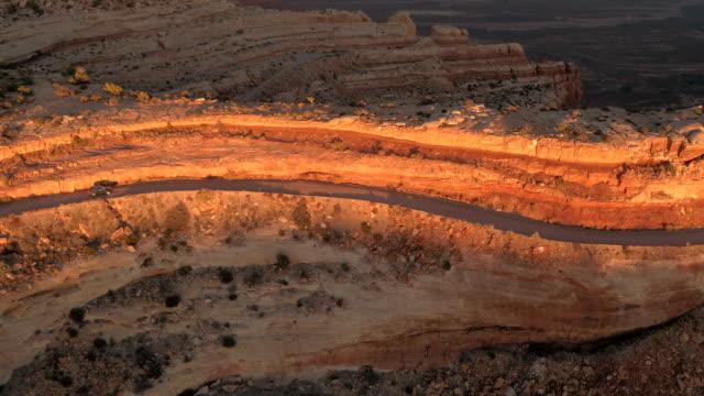 AERIAL Black SUV car driving on winding Moki Dugway mesa mountain pass at sunset video