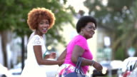 Black woman and adult daughter walking down city street video