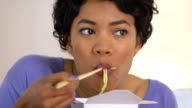 Black woman eating noodles from Chinese takeout video