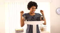 Black woman excited about weight loss on scale video