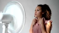 Black woman feeling hot and sitting in front of an electric fan to get some cool air on her face video