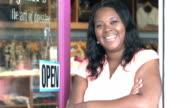 Black woman hanging OPEN sign on door of clothing store video