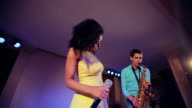 Black woman singer and thin saxophone player performing on stage. video