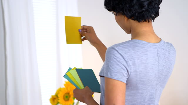 Black woman using paint chips to pick out color video