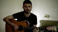 A black-haired guy playing the guitar. video