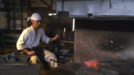 Blacksmith adding coal to the furnace video