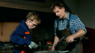 HD DOLLY: Blacksmith Assisting A Young Trainee video