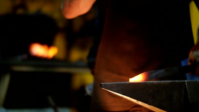 Blacksmith Banging with a Hammer on a Hot Metal in a Workshop Slow Motion video