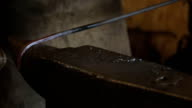 Blacksmith bends metal rod on anvil with hammer blows video