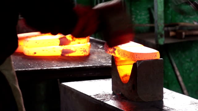 Blacksmith forges a red-hot iron in the forge video