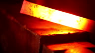 Blacksmith forging red hot iron on anvil, extreme closeup video