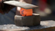 Blacksmith hammering hot round metal to shape it video