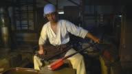 Blacksmith inspecting a block of beating metal video