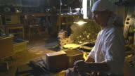 Blacksmith pumping the bellows for fire in his furnace video