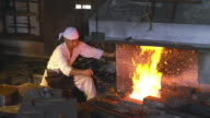 Blacksmith pumping the bellows of his furnace video