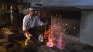 Blacksmith pumping the flames in his furnace video