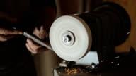 A blacksmith sharpening a workpiece on a grinding lap closeup video