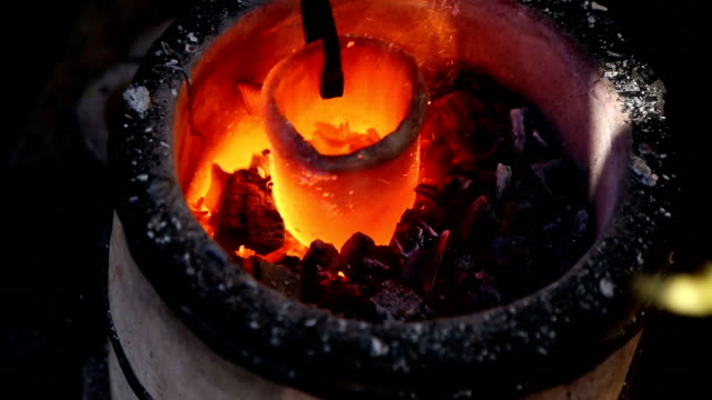 Blacksmith tongs pulls a red-hot crucible with the metal from the hearth video