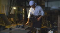 Blacksmith using hammer to shape metal video