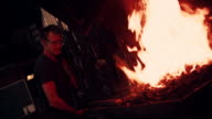 Blacksmith working iron on a forge with fire in Slow Motion video