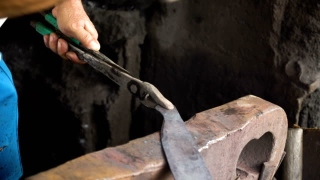 Blacksmith working metal with hammer video