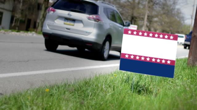 Blank political sign near busy road in suburban neighborhood in daylight video