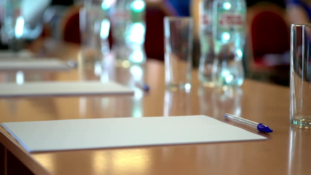 A blank sheet of A4 paper on the table with a pen. A business audience (school class) video