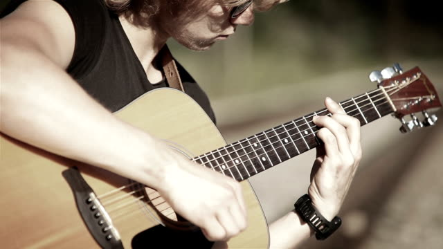 Bleak footage of a long-haired guitarist playing a song in simple chords video