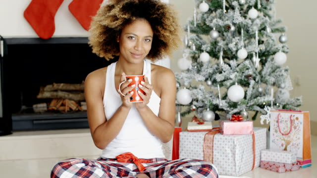 Blissful young woman drinking coffee at Christmas video